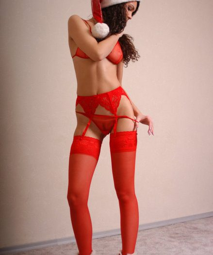 Youthfull marvelous sensuous Santa Claus poses indoor.