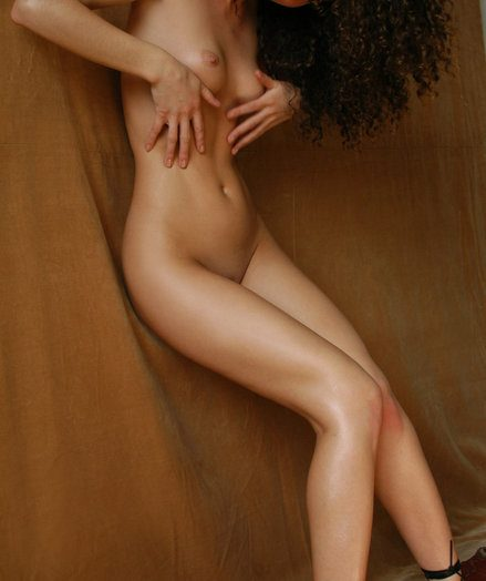 Curly youthful lady with sumptuous host poses empty indoor.