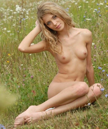 Towheaded luxurious angel with slender figure poses naked on rub-down the spring field.