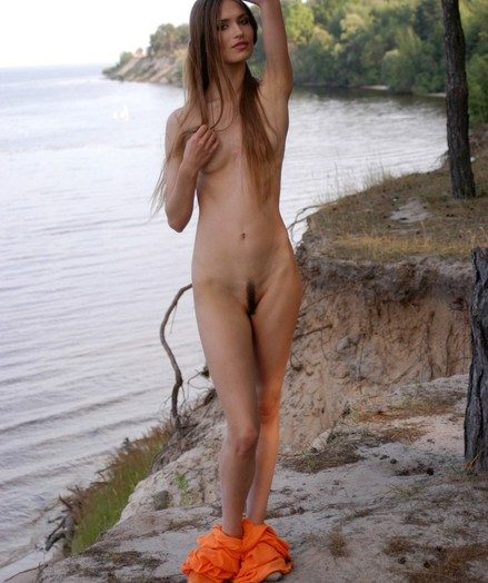 Slender splendid generalized with reference to lengthy hair takes her clothes lacking and poses bare on the beach.