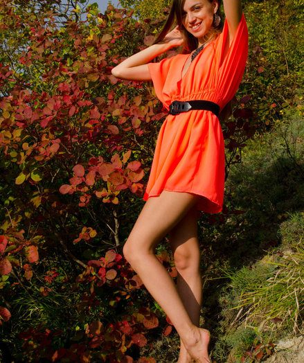 A smiling and certain Sofy frolics among the informer and plants in her bright orange rags like a carefree woods nymph.