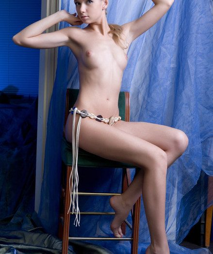 Explicit posing coupled by a shy smile on a pretty face, against a soddening blue background.